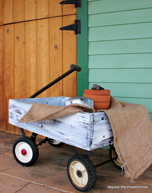 use pallet wood and old wheels to make a wagon for the porch