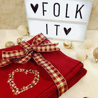 Red cotton napkins, folded. Handpainted with a heart made of leaves and dot roses. The napkins are sat in front of a light box containing the words Folk It
