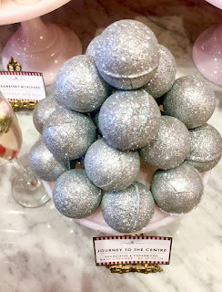 Spherical glittery bath oils in a clear glass bowl oon a bright background