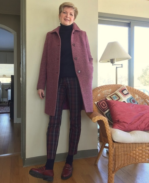 woman in plaid pants, navy sweater and socks, fuchsia tweed coat, and burgundy loafers leaning against a wall