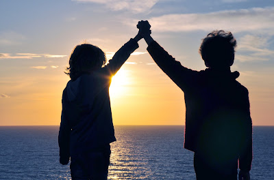 PIc of two children's silhouettes against sunset over sea