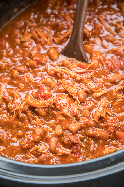 Slow Cooker Pulled Pork Chili - our all-time favorite chili! Pulled pork, Bush's chili beans, Hunt's Petite diced tomatoes, Hunt's tomato sauce, Ro*tel diced tomatoes and green chilies, chili seasoning, minced onion, and tomato juice. Just dump everything in the slow cooker and let it work its magic! Makes a ton - great for tailgating, potluck, holiday get-togethers. Can freeze leftovers for a quick meal later! LOVE this chili!!! #ad #WMChiliPride #slowcooker #chilirecipe