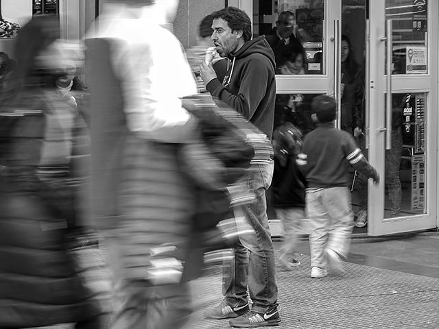 Hombre de pie tomando helando mientras a su alrededor pasa gente.BYN