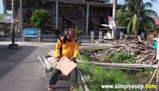 LEMPAR : Kayu dan pecahan papan yang sudah tidak terpakai bisa dilemparkan ke dalam tempat yang sudah disediakan untuk dibakar tuntas. Foto Asep Haryono