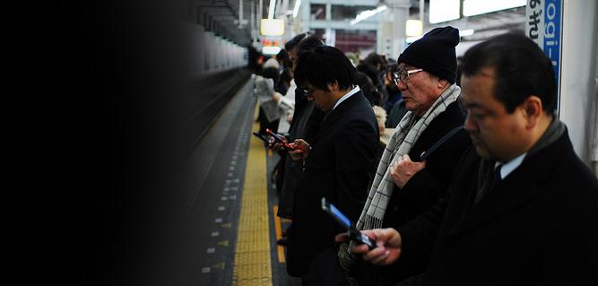 Japonseses esperando el metro viendo sus teléfonos