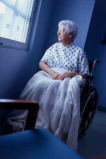 An elderly woman sits along in a wheelchair in her room.