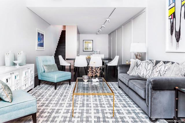 Bright living room in a Sydney loft with a geometric rug, grey sofa with nail head trim, turquoise chairs, a long white side table, and a glass coffee table with gold trim