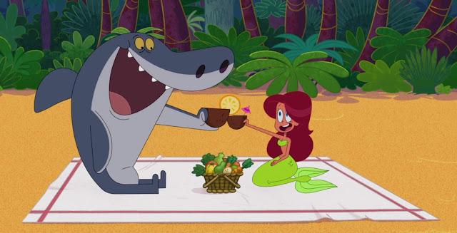 sobre una toalla de playa Sharko y Marina brindan con cocos y en medio tienesn una cesta lena de verduras y frutas