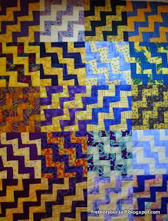 Purple and gold printed fabrics alternate across this quilt.