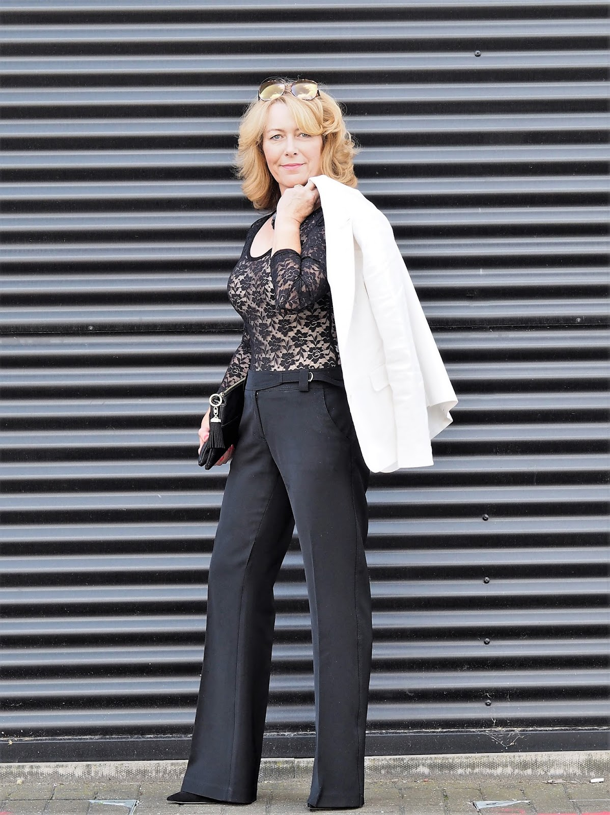 Laurie Bronze from Vanity and Me in black lace top and elegant black tailored trousers