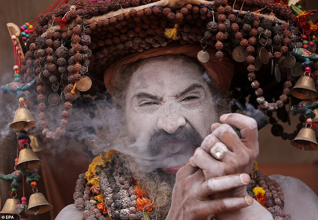 An Indian Naga Sadhu or naked holy man smokes marijuana from a clay pipe in his tent near Sangam river