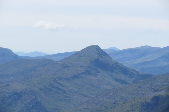 Close-up of the pyramidal summit of Yr Aran, with hazy mountain tops in the background.