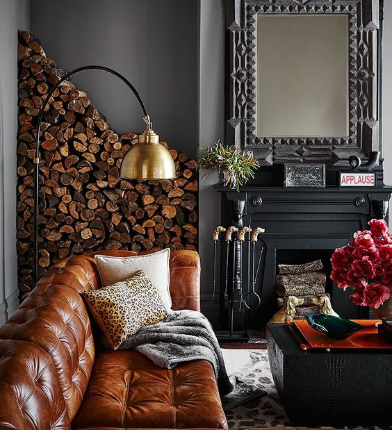 Dramatic grey walls black fireplace wood stack leather sofa Ken Fulk