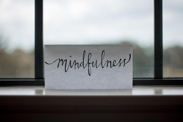 um papel com a palavra mindfulness escrito, colocado sobre o parapeito da janela