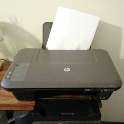 HP printer pulling a sheet of paper into the device by one side.