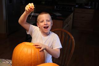 boy carving a pumpkin