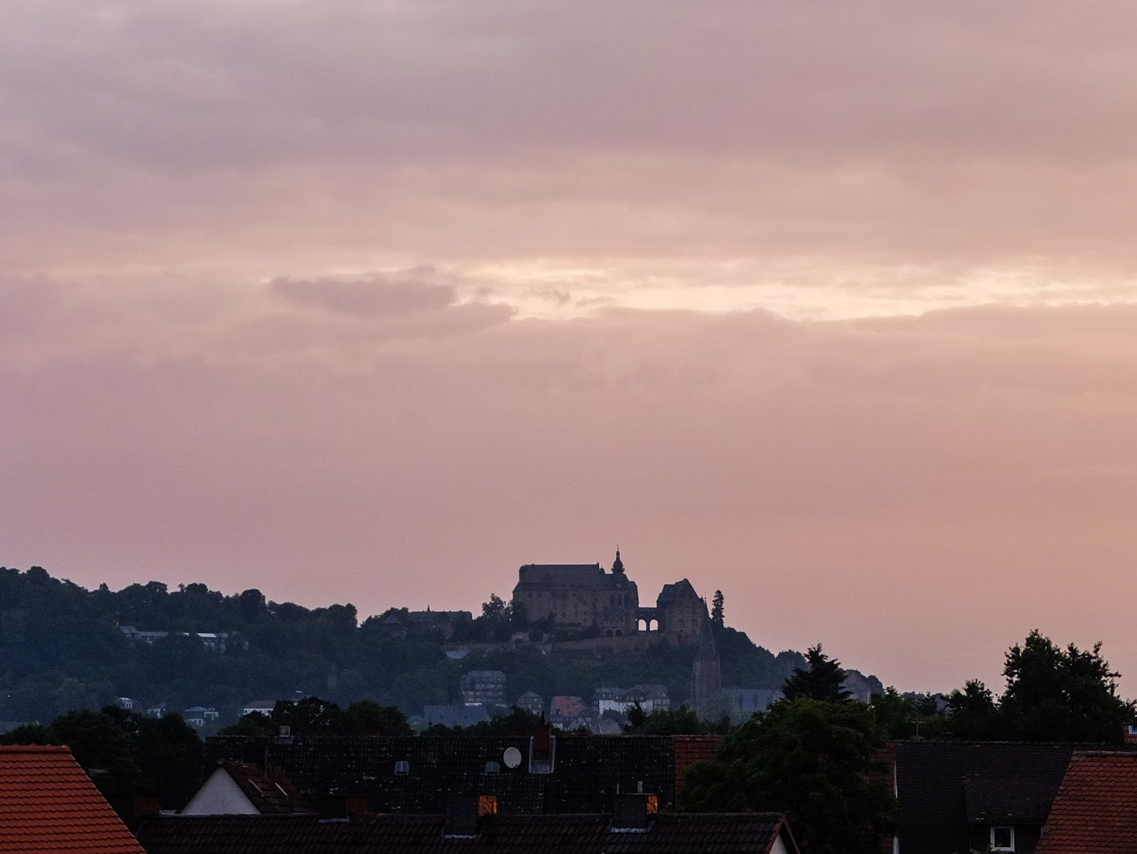 View of the Marburger Schloss at sunrise overlooking terracotta tiled roofs.