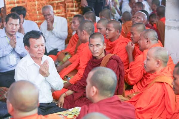 Opposition leader Kem Sokha sits in the center of a crowd of monks and supporters during a recent Buddhist ceremony outside the Cambodian National Rescue Party headquarters in Phnom Penh. KT/Mai Vireak