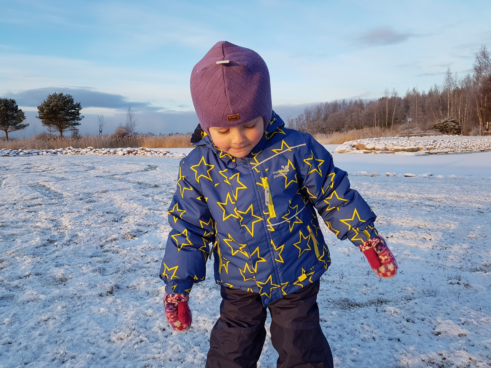 child standing in snow and wearing ski clothing