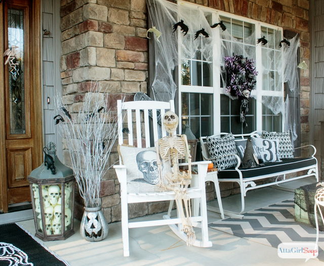 Front porch with lantern full of skulls and skeleton sitting on chair