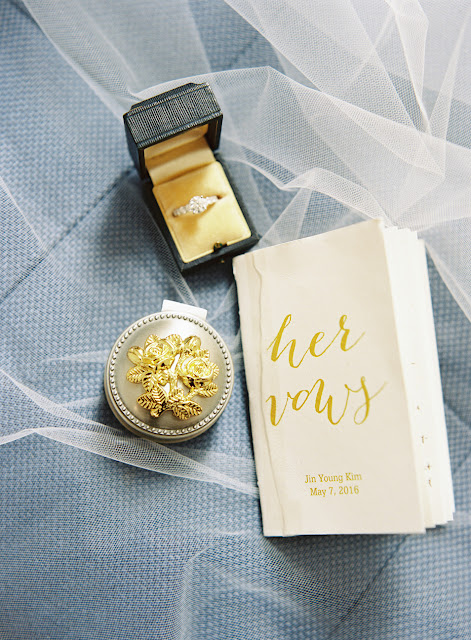 Jin's delicate book of vows, wedding ring, and jewelry case arranged atop her veil