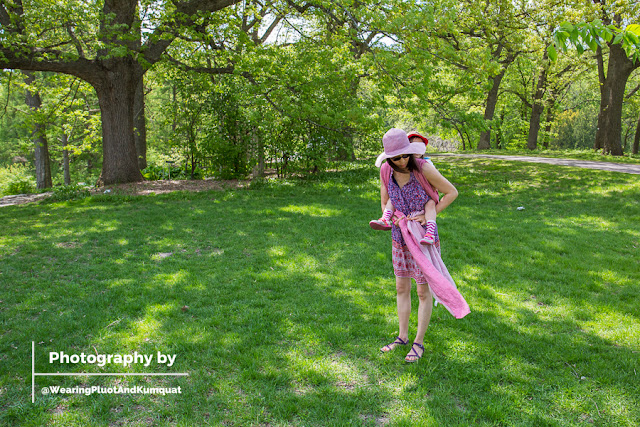 [Photograph by my husband. Image of me, a light tan skin Asian woman wearing sunglasses and a floppy purple sun hat. I have a preschooler on my back in a pinkish reddish linen woven wrap. I am holding on to the tails at my waist and about to complete the rucksack back carry with a Tibetan finish. We are outside on a gorgeous spring day with green grass and sparkling trees.]
