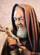 Padre Pio vestido de fraile capuchino y mirando el crucifijo que tiene en las manos