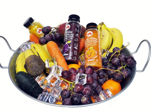 una bandeja de metal llena de frutas,hielos y tres botellines de zumo vibs