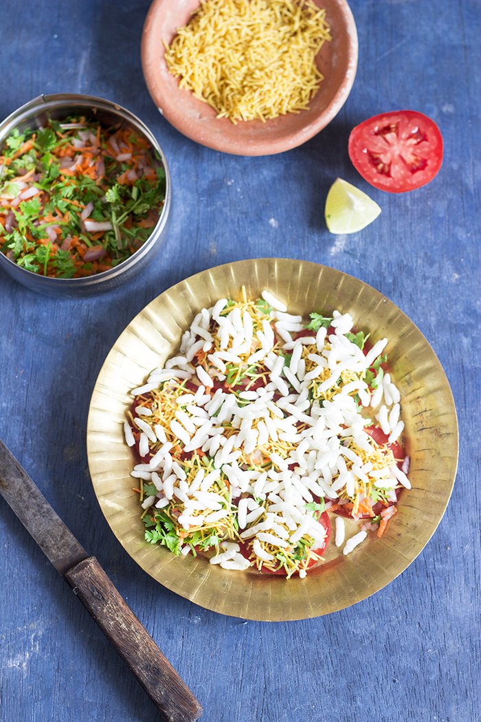 Bangalore Street food made by topping tomato slices with a mix of sweet and spicy chutneys and topped off with salted puffed rice