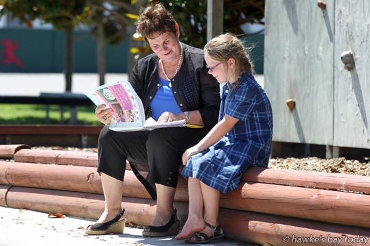"L-R: Sandra Connor, principal, St Joseph's School, Hastings, with Jean-Anne Harrison, 6, year two, looking over ""Jean-Anne's Holiday Writing"" after her first day back at school after the holidays. photograph"