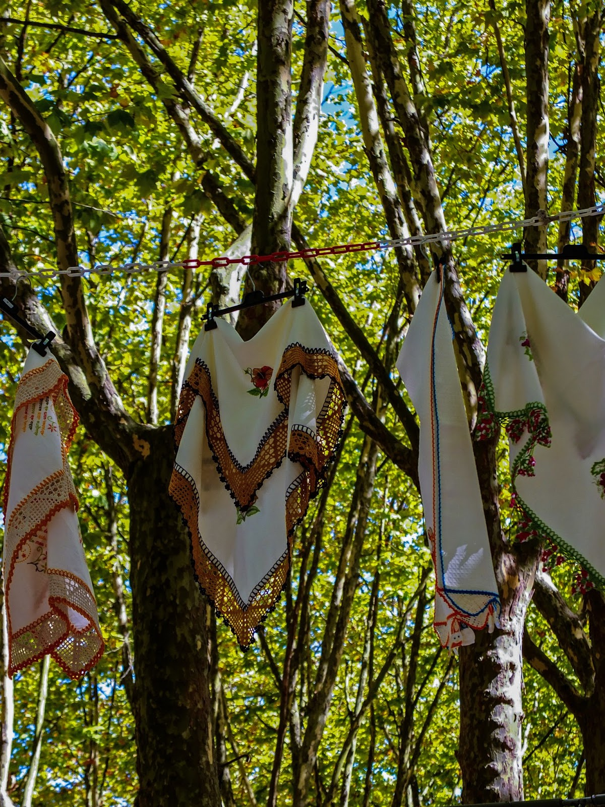 Handmade cloths hanging between trees at a market in Porto, Portugal.
