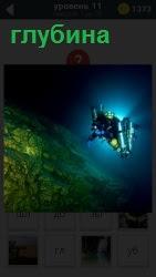 На большой глубине плывет аквалангист с освещением