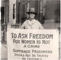 Picture of a woman Suffragette, black and white photo, holding a sign asking for freedom