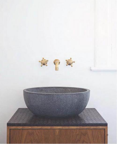 über einem Steinwaschbecken ist ein goldener Wasserhahn angebracht