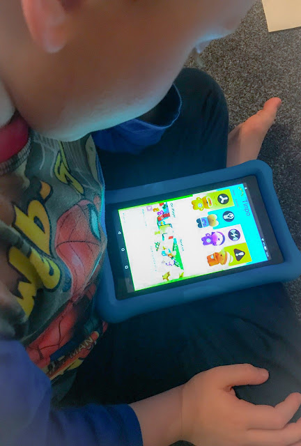 Side view of a little boy watching Tinpo on a kid friendly tablet