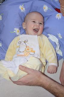 Baby lacht weil mit seinen Beinen gespielt wird