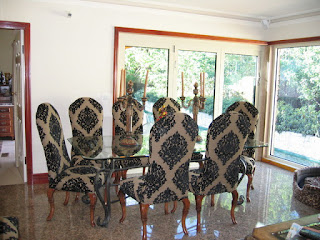 Artistic Upholstered Dining Chairs around the Glass Table and Classic Iron Candle Handles in Classic Dining Room