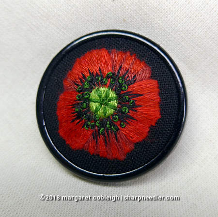 Completed embroidered remembrance poppy mounted in a round black pin setting