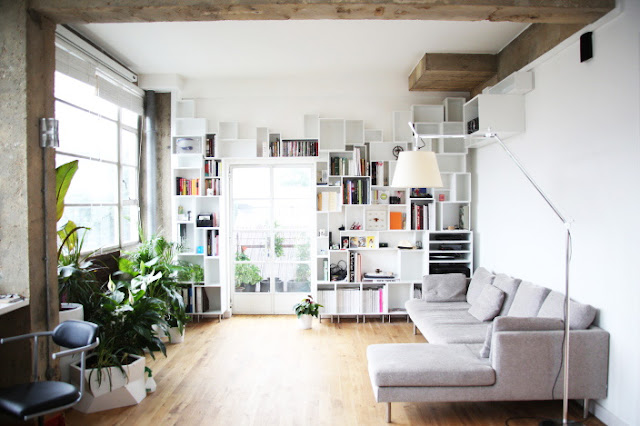 living room with gray sectional, built in bookshelves, exposed beams and potted plants