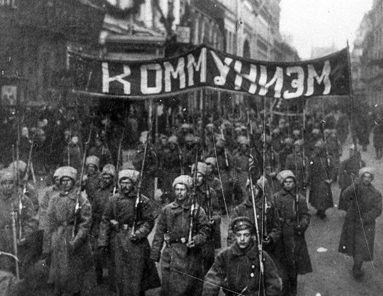 Soldados com a faixa COMUNISMO marcham rumo ao Kremlin pela rua Nikolskaya