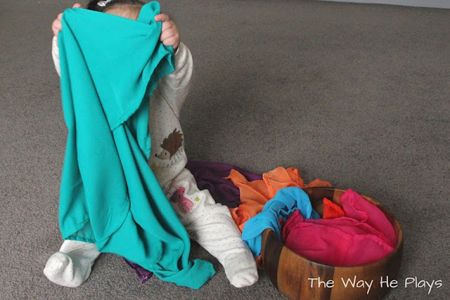 Baby playing peek a boo with a play silk