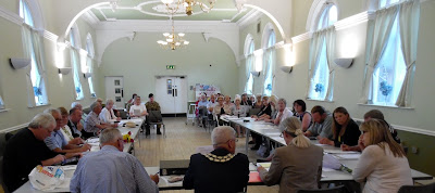 PICTURE: A meeting of Brigg Town Council  in 2018 with the public gallery at the far end of the Angel Suite. Town Mayor Coun Donald Campbell, nearest the camera - wearing his chain of office - is chairing the session. Town councillors are seated left and right. Image on Nigel Fisher's Brigg Blog