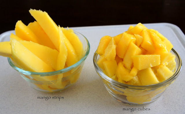 Two small bowls on a table, one with sliced mango and one with cubed mango in them