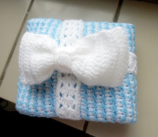 folded crochet baby boy blanket tied up with crochet ribbon