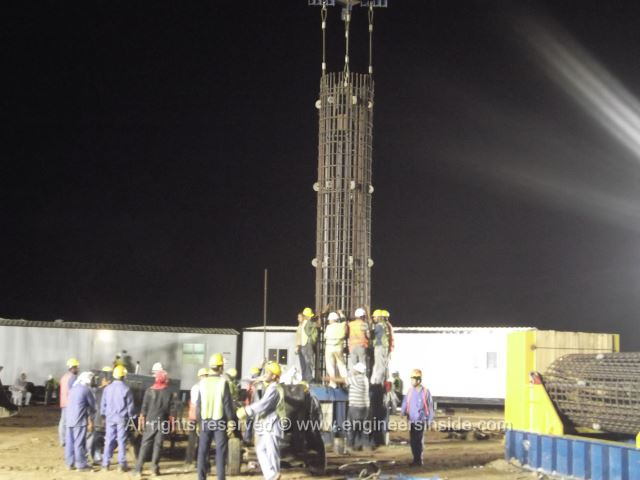 Test pile being lowered into place by the crane and a lot of workers