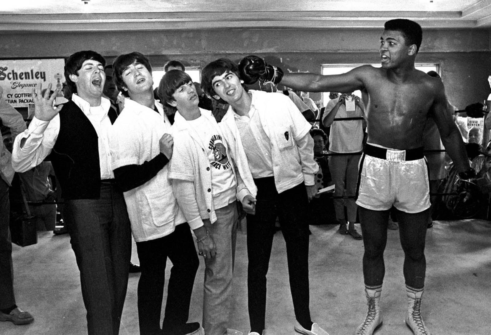 The Beatles take a fake blow from Cassius Clay, who later changed his name to Muhammad Ali, while visiting the heavyweight contender at his training camp in Miami Beach, Florida, on February 18, 1964.