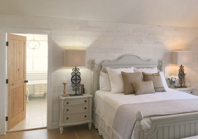 master bedroom with stikwood wood plank wall and knotty alder door to bathroom in Hello Lovely Studio fixer upper