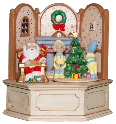 A hand-made ceramic music box showing the living room of Santa, with him asleep in a rocking chair, and elves decorating the tree.