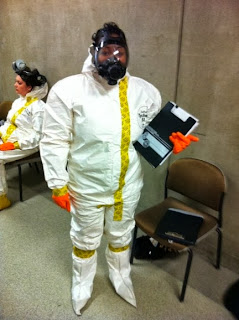 Dr. Drake gets ready to work in a clandestine lab in a haz-mat suit.