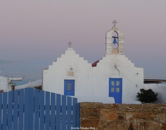 Białe kaplice z niebieskimi drzwiami na tle purpurowego greckiego nieba Mykonos Grecja